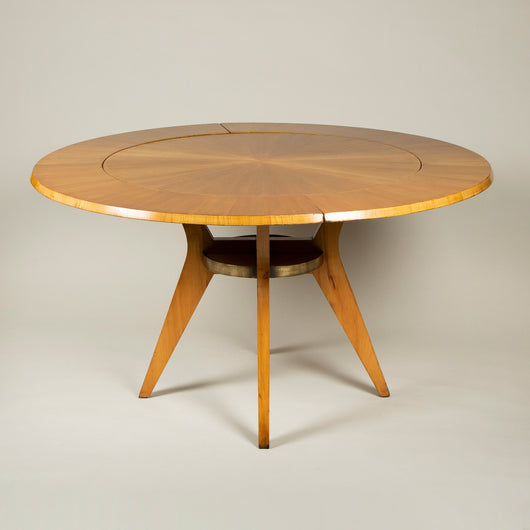 A mid 20th century French birchwood round table, the segmentally veneered top with two detachable extending leaves and four incurved legs joined by a brass-edged ring stretcher.
