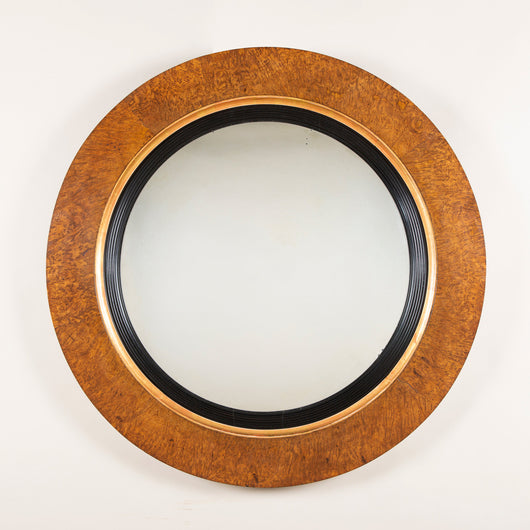 An unusual convex mirror, the flat burr oak frame with a gilt and ebonised reeded slip. English ca. 1820.