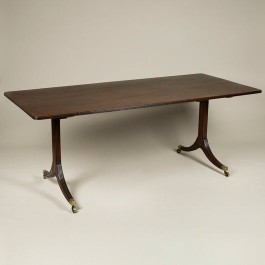 An elegant Regency mahogany writing table, the unusually wide top with reeded edges and two moulded and reeded side supports on splayed feet. English, circa 1810.