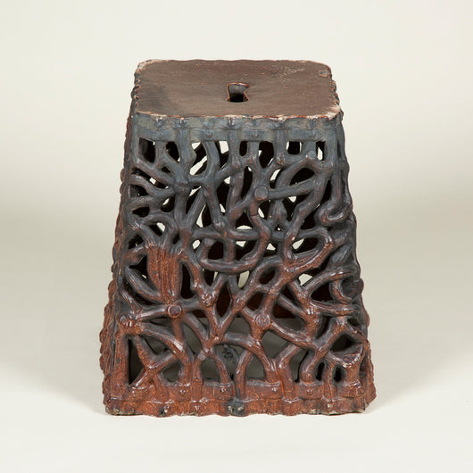 A late 19th century ceramic garden seat of square tapered shape and open fret vermiculated sides, with a dark brown glaze.