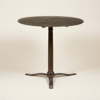 A late 19th or early 20th century round iron table with a central fluted column support and three splayed flat feet.