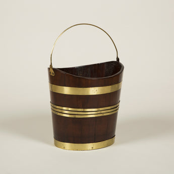 An 18th century brass-bound mahogany oval coopered bucket with swing handle.