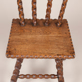 A small stick-back elm chair with notched tramp art spindles and legs. Early 20th century.