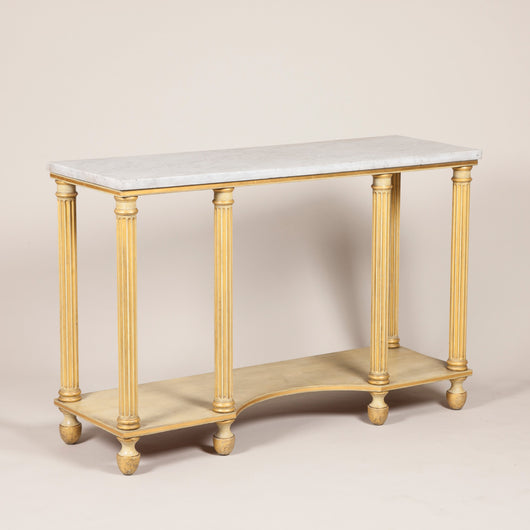 An early 19th century painted and gilded console table with column supports and a concave centre, circa 1820.