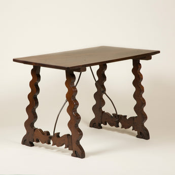 A rectangular mid -18th century Spanish walnut table, the four flat legs with serpentine edges joined by cross stretchers and a curved wrought iron brace.