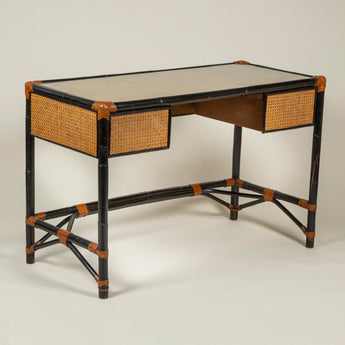 A French 1950's lacquered bamboo knee-hole desk with leather binding, caned panels and a glass lined top.