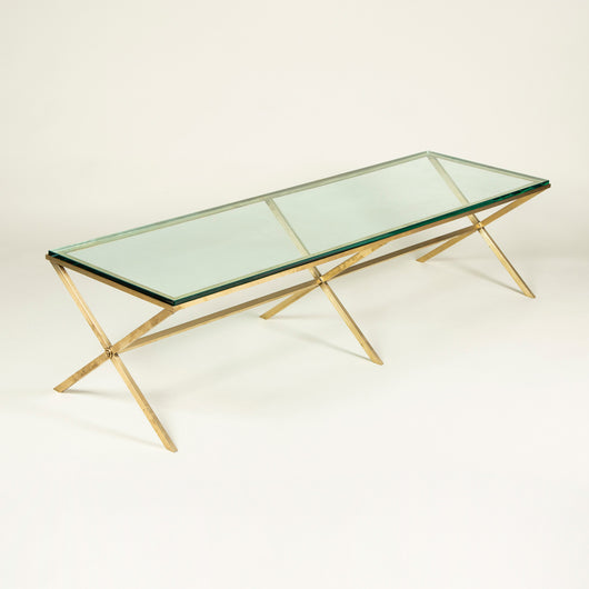 A long rectangular glass-topped coffee table with a triple X-frame brass understructure, circa 1960's.