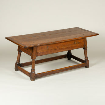 A low 19th century oak and pine table with splayed turned legs joined by stretchers and a single frieze drawer.