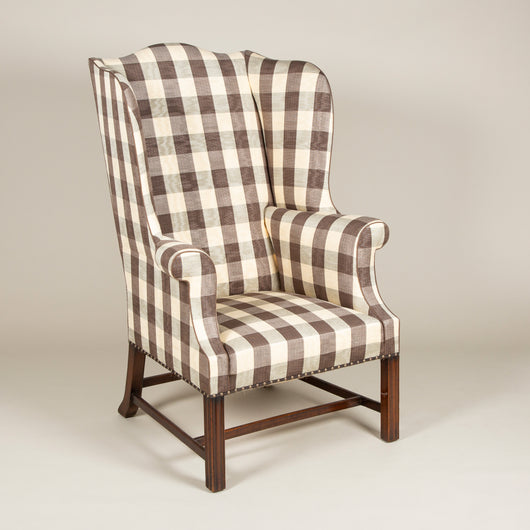 A high-backed Chippendale period wing arm-chair with mahogany moulded legs and cross-stretcher. English, circa 1770.