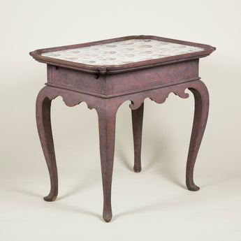 A rectangular Swedish burgundy-painted tray-top table inset with manganese and white delft tiles and with a scrolled apron and cabriole legs, circa 1760.