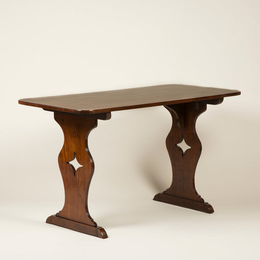 A late 19th or early 20th century Arts and Crafts side table with pierced side supports.