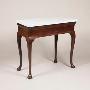 An unusual George II mahogany side table, circa 1750, with tapering veined Carrara marble top, cabriole legs and pad feet.