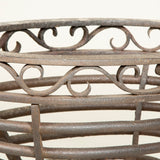 An English wrought iron fire basket. The oval basket resting on scrolled supports and flanked either side by serpent handles. Circa 1900.