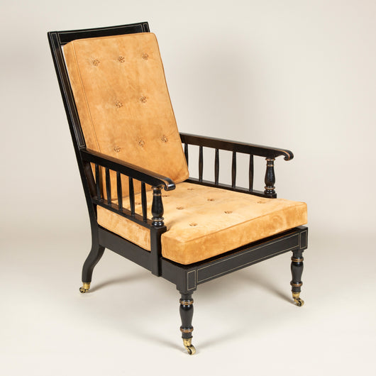 A large ebonised stick back armchair, mid-19th century. The white-lined ebonised finish restored in parts, the suede-covered back and seat cushions new.