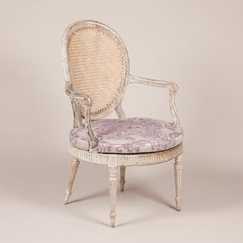 An elegant 18th century English open armchair with an oval caned back and caned seat. George III circa 1790. Distressed original paintwork.