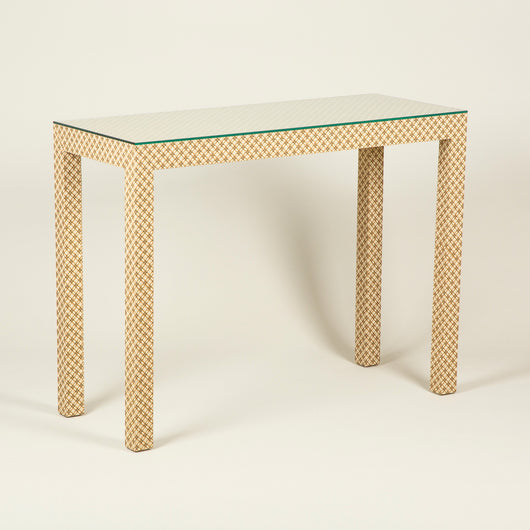 A fabric covered console table of simple form, with a glass top. Made to order.