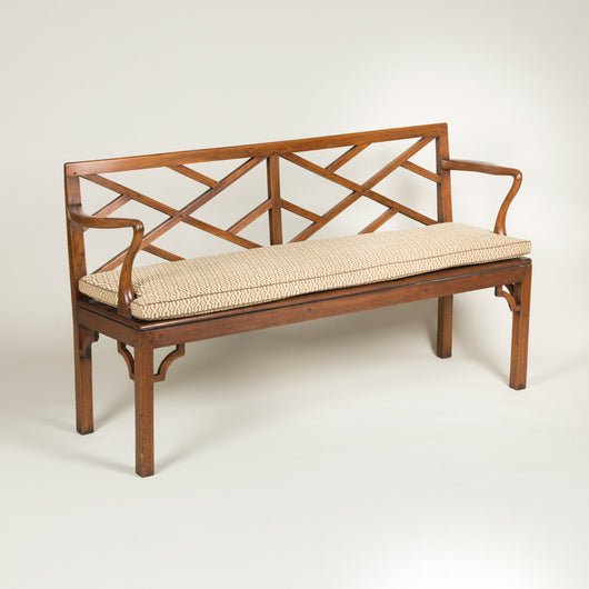 A charming elm and walnut hall bench with a low Chinese lattice back and crook arms. English, late 18th century.