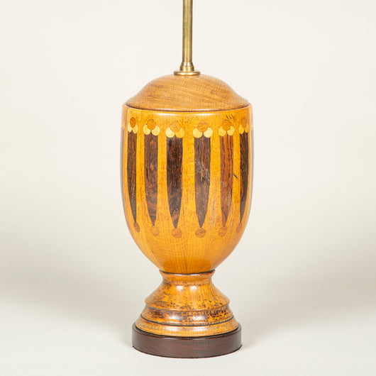 A turned wood urn decorated with geometric marquetry, early 20th century, wired as a lamp.