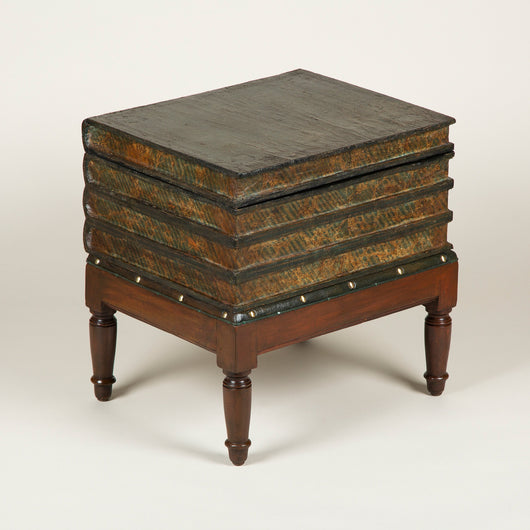 A low table in the form of a pile of books on a four legged-stand, the top book in the pile opening on a hinge with a compartment underneath. French, early 19th century.