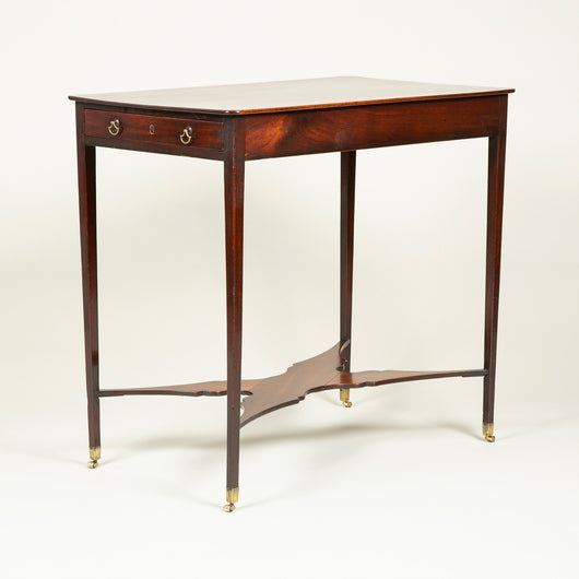 A small George III mahogany rectangular writing table with two drawers and slender tapering legs joined by a shaped stretcher, circa 1770.