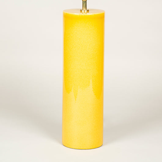 A pair of tall cylinder-shaped pottery lamps with a deep yellow glaze.