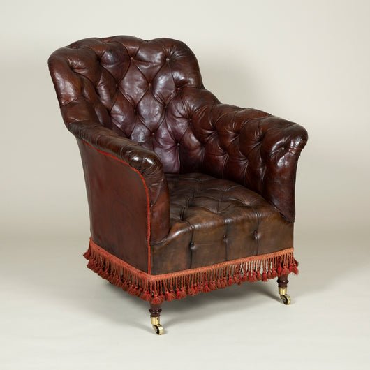 A 19th century deep buttoned leather armchair with high downswept arms and turned legs, the base trimmed with tassel fringing.