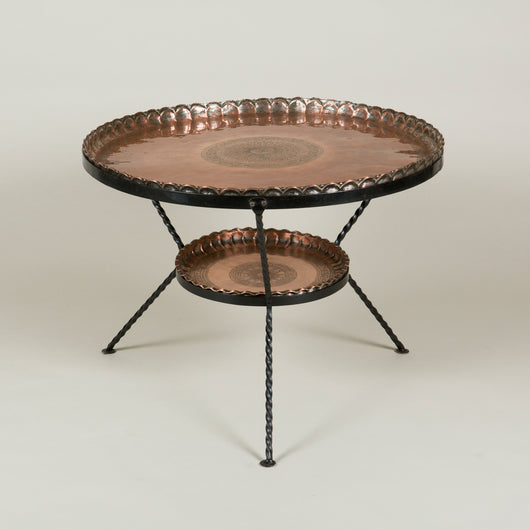 An early 20th century Moroccan two tier round table, the engraved copper tiers supported by a blackened steel stand.