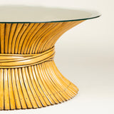 A low 1970's American coffee table designed by McGuire in the form of a bound sheaf of bamboo with a new glass top.