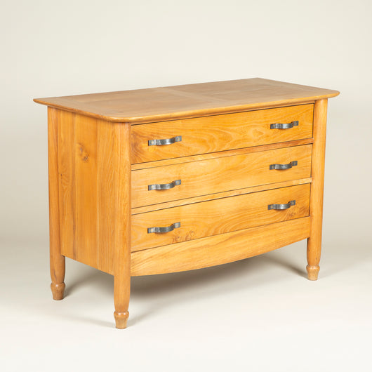 A French elmwood chest with three drawers, flat metal strap handles and turned front legs, circa 1960.