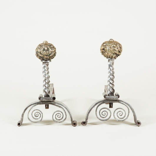A pair of wrought iron fire dogs with spiral twisted uprights and brass ball finials with grotesque repousse decoration. 19th century.