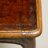 An unusual Louis XV oak writing table with a red leather-lined top, an elegant serpentine apron and slender cabriole legs. Traces of original paint. French, circa 1760.