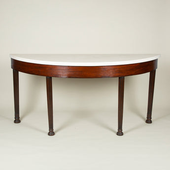A large 19th century mahogany-veneered freize supported by four legs made from 18th century bed-posts, possibly made by a country-house estate carpenter, with a replacement limestone top.