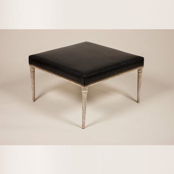 A square stool with a leather-upholstered seat on a grey-painted under frame with tapering spiral-fluted legs. Maison Jansen, Paris, circa 1950.