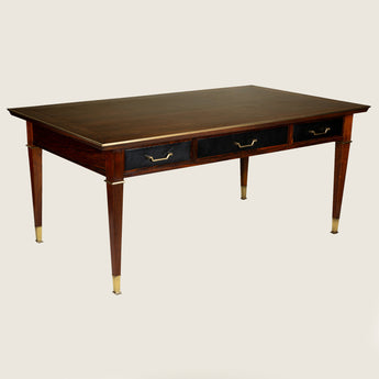 A mid 20th century rosewood writing table with a brass-framed top, leather-covered drawers to the front and back and square section legs with brass collars and brass sabot feet.