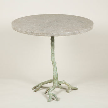 A rustic painted metal table in the form of branches topped with a new fossilised marble top.