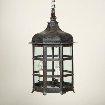 An Arts and Crafts iron octagonal hanging lantern with a facetted ogee top. Rewired.
