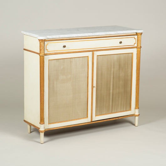 A Regency white-painted and parcel gilt side cabinet with original white marble top and two doors with pleated silk panels enclosing shelves. English, circa 1810, decoration refreshed.