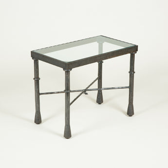A rectangular Giacometti style side table in bronze with an inset glass top.