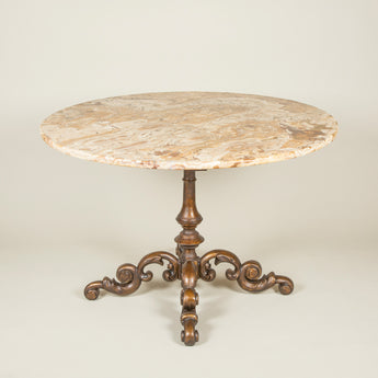 A round center table with a heavy 19th century cast iron base with four scrolled feet and an associated Egyptian marble top.