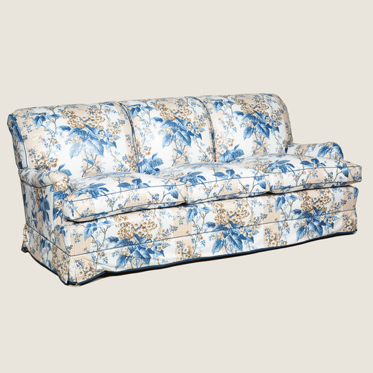 A large three seat sofa in a traditional style upholstered in a floral chintz fabric in blues and browns on a white ground.