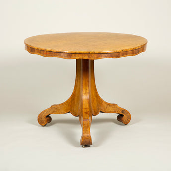 A Biedermeyer amboyna and walnut veneered round table with cross-banded undulating apron and gently concave splayed triform base with scrolled feet. Austrian or Baltic, circa 1840.