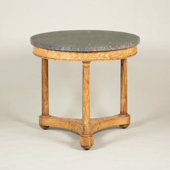 An early 19th century Continental burr elm veneered gueridon with an old marble top and a lower tier.