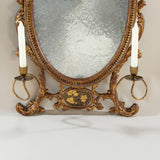An elegant Adam period oval girandole or dressing mirror, the gilt carved wood and composition frame with an anthemion crest, two flanking candle arms and a panel of Chinese lacquer at the base. English, circa 1770.