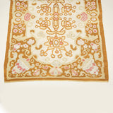 A 19th century Bessarabian rug with all-over formalised floral motifs in pink, white and pale yellow on a tan ground with a central white reserve.