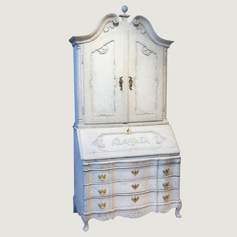 A white-painted Rococo bureau bookcase, the upper part with two carved doors, the lower part with a drop-leaf writing compartment over drawers. Danish, circa 1760, the paintwork possibly later.