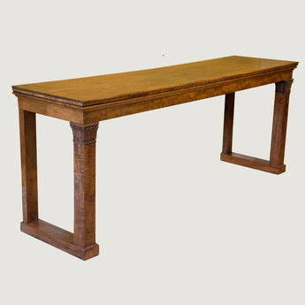 A wide rectangular early 19th century mahogany serving table of simple form with good colour and figuring; square section ends supports with acanthus carved capitals. English, circa 1830.
