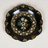 A scalloped papier mache dish with inlaid mother of pearl and floral decoration.