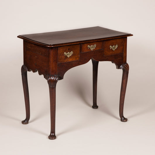 A George II provincial oak lowboy with an ogee apron and three frieze drawers, circa 1770.