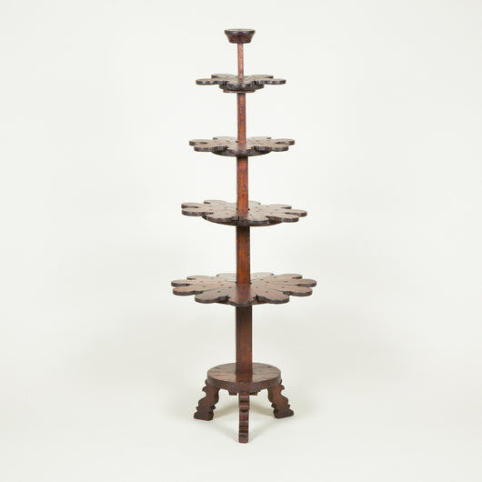An unusual wooden plant or lamp stand with four graduated tiers on a central support. South India.
