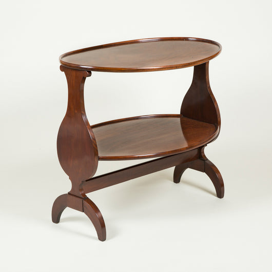An early 19th century French mahogany two tier table with a tray top and baluster shaped end supports.